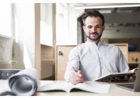 微笑的年轻人坐在办公室的椅子上工作_4831052
