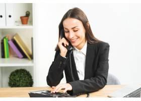 微笑的年轻女商人在办公室里打电话_3930743