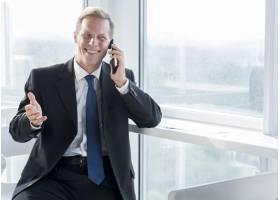 微笑的成熟商人用手机交谈_3105768