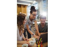 一群企业高管在他们的DES上讨论笔记本电脑_1006050