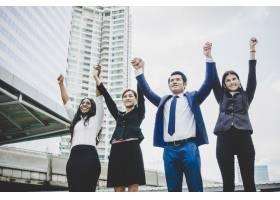 一群快乐的年轻生意人手举着手成功地完成_1603425