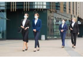 一群穿着西装戴着口罩的女经理一起走过_9649748