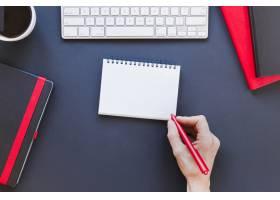 不知名的人在咖啡杯和键盘旁的笔记本上写字_5471476