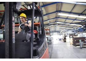 专业工业女司机在工厂仓库操作叉车机_11036095