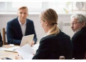 专注严肃的女商人在小组会议或谈判中阅读_3954474