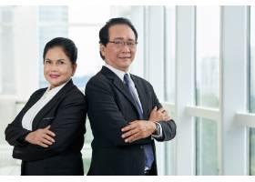 两个商务人士背靠背站在办公室窗口的肖像_5766957
