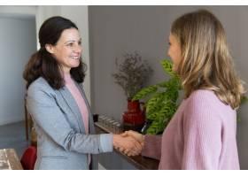 两个微笑的女人站着握手_4167263
