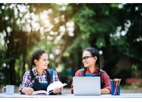 两名学生在公园里用笔记本电脑在线学习_2525703