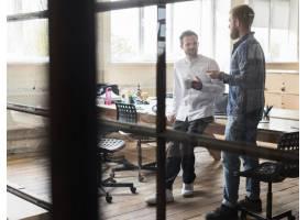两名男性商人在工作场所交谈_4857490