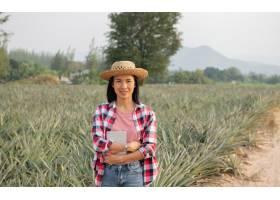 亚洲女农民在农场看到菠萝的生长农业产业_13013468