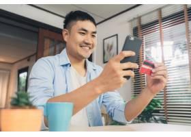 亚裔男子在客厅家中用智能手机网购用信用_3441199