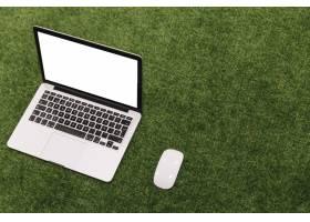人造草地背景下的开放式笔记本电脑和鼠标_3006130