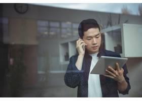 企业高管一边使用数字平板电脑一边打手机_8237349