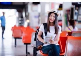公交车站拿着地图和包微笑的亚洲美女_5017106