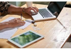 剪裁男子在纸上画项目并使用笔记本电脑的特_5699078