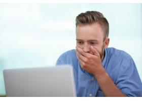 震惊的年轻人在笔记本电脑上工作的特写_992747