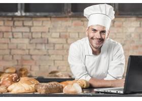 面带微笑的男面包师在厨房台面上放着不同类_2976604