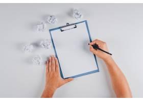 顶级人物在剪贴板上用皱巴巴的白纸写字_7711609