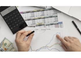 顶视图的商人正在研究图表_11621125