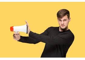黄色录音棚背景上拿着扩音器的年轻人_11314307