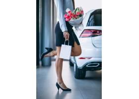 汽车陈列室里拿着鲜花的女人_4202522