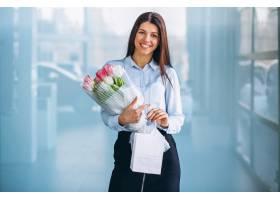 汽车陈列室里拿着鲜花的女人_4202523