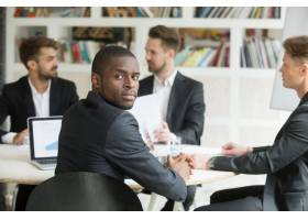 自信的非裔美国商人坐在会议上看着摄像机_3938101
