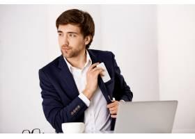 英俊的成功商人坐在办公桌上喝着咖啡在_9226872