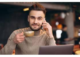 英俊的生意人在咖啡馆里一边用电脑一边喝咖_4209702