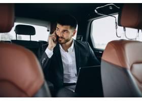 英俊的生意人在车里用电脑工作_5508199