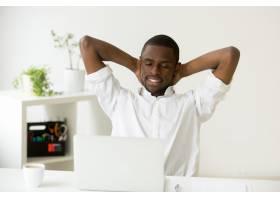 满意的快乐的非裔美国人用咖啡和笔记本电脑_3938082