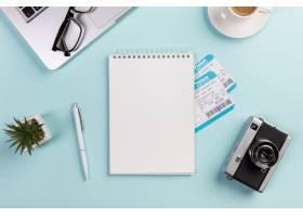 蓝色桌子上的空白螺旋记事本机票周围有笔_4743279