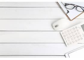 白色整洁的桌子上有眼镜计算器和平板电脑_1168078