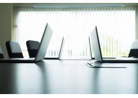 电脑笔记本电脑放在会议室的桌子上_1235696