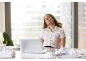 疲惫的女商人睡在办公桌前的椅子上_3938722