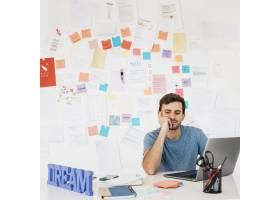 疲惫的年轻人坐在手提电脑旁边拿着笔记靠_5000074