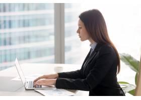 成功的严肃的商务女士使用笔记本电脑在办公_3938484
