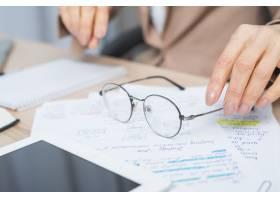 妇女手持眼镜遮住文件的特写镜头_3707729