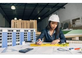 戴安全帽的非裔美国妇女在建筑模型附近工作_3706624