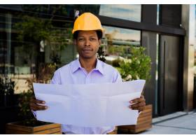 戴着头盔的专业建筑师的肖像看着现代建筑_9882711