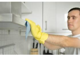戴着橡胶手套的男性手清理抽油烟机的特写_1281463