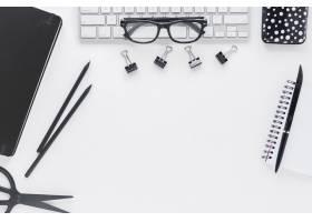 工作场所的键盘上有文具和眼镜_5471469