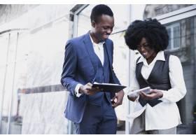 手持剪贴板和数字平板的微笑的非洲年轻商人_4765061