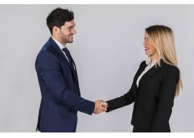 年轻的商人和女商人在灰色的背景下握手_4502578