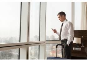 年轻商人在酒店房间里使用智能手机_1280444