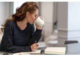 年轻女子在家工作厨房里用记事本她正在_11961323