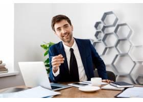 年轻成功的商人坐在工作场所有办公室背景_7855220