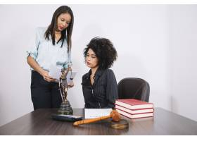 拿着文件的非洲裔美国妇女坐在桌子旁拿着计_3741124