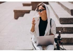 年轻的女商人手持笔记本电脑坐在楼梯上_5494982