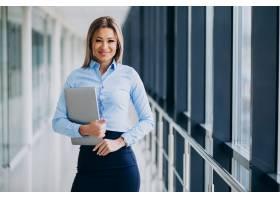 年轻的女商人拿着笔记本电脑站在办公室里_7200193